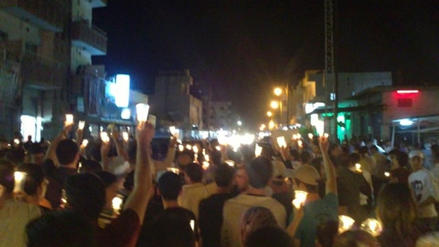 May 10: In this citizen journalism image made on a mobile phone and acquired by the AP, Syrian anti-government protesters carry candles during a rally in the northeastern city of Qamishli, Syria.