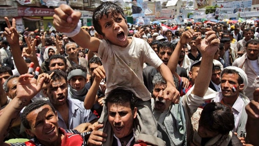 May 10: A Yemeni boy lifted by anti-government protestors reacts during a demonstration demanding the resignation of Yemeni President Ali Abdullah Saleh, in Sanaa, Yemen.