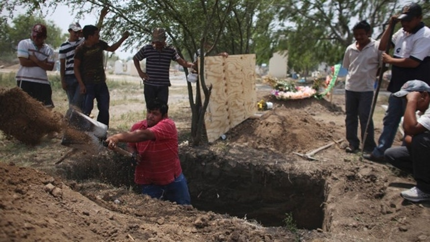 April 27: Family members of Alfredo Espinosa, allegedly killed by unknown assailants, dig a grave at a local cemetery in San Fernando, Mexico.