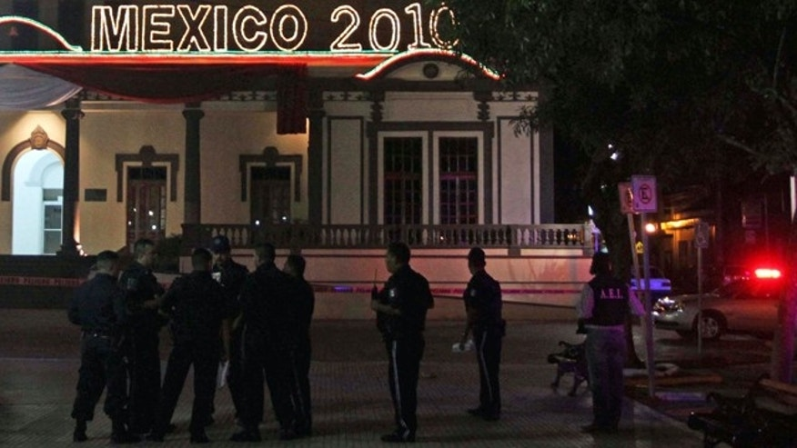 Police officers stand at the area where a grenade was detonated by unidentified people, leaving at least 12 people injured, in front of the town hall in the municipality of Guadalupe, outskirts of Monterrey, northern Mexico, late Saturday, Oct. 2, 2010.  (AP Photo/Carlos Jasso)