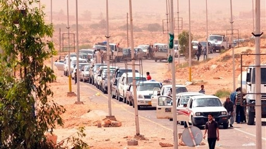 Libyans flee from fighting as they cross the Dhiba border between Libya and Tunisia, Sunday, May 1, 2011. A battle between Libyan troops and rebels spilled over the border into Tunisia Friday, drawing a sharp rebuke of Muammar al-Qaddafi's regime from the neighboring government. The Tunisian army stopped members of Qaddafi's brigades, regrouping them and leading them back to Libyan territory, the Tunisian Defense Ministry said, and the Tunisian news agency, TAP, citing military officials, said dozens of Libyan troops and rebel fighters were killed in the two-day battle over the Dhuheiba crossing which ended with rebels regaining control Friday, after Libyan forces held it for a day. (AP)