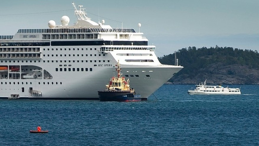 May 16: The cruise ship MSC Opera, left, carrying about 1,800 passengers, is towed into the Swedish port of Nynaeshamn.