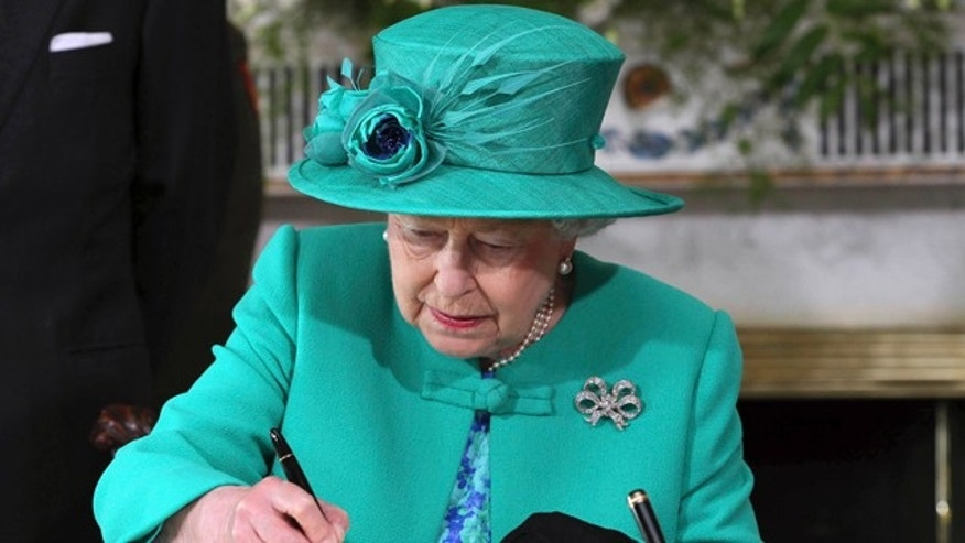May 17: Britain's Queen Elizabeth II signs the visitor's book at Aras An Uachtarain, the Irish President's residence in Phoenix Park, Dublin.