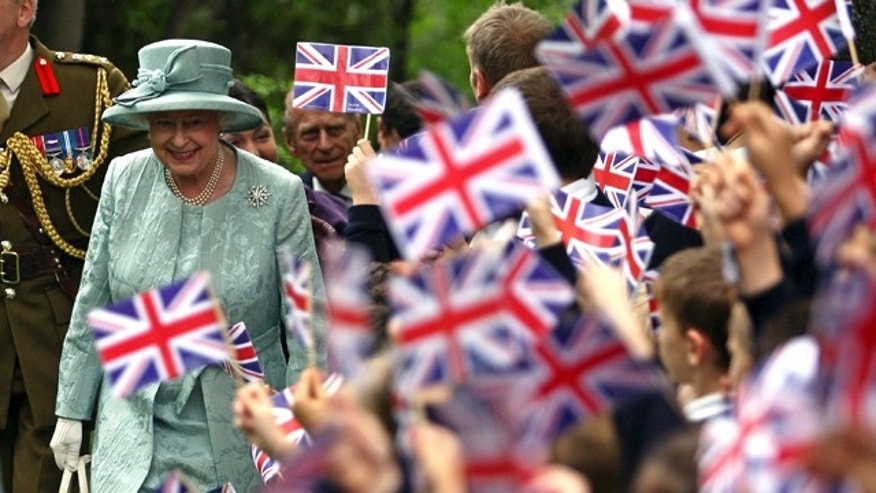In this May 16, 2008 file photo, Britain's Queen Elizabeth II, left, is welcomed by children waving Britain's flag, upon her arrival at the British Embassy in Ankara, Turkey.