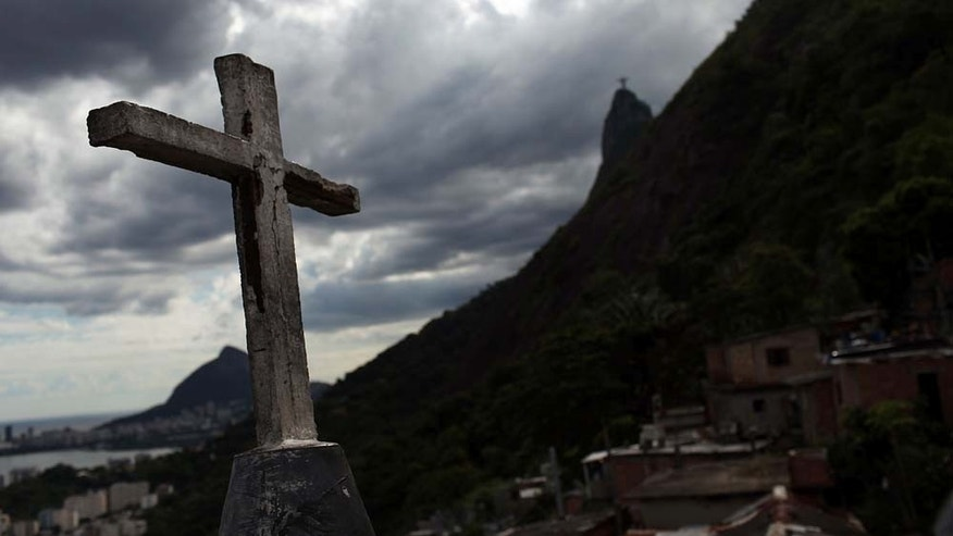 "RIO DE JANEIRO, BRAZIL - DECEMBER 03: A church cross stands over recently ""pacified"" Santa Marta, one of Rio's oldest slums, or favela on December 3, 2009 in Rio de Janeiro, Brazil. Santa Marta is one of a number of Favelas in Rio where the police are attempting a softer touch by participating in community policing after they clear the area of drug gangs. It is believed that the police want to continue with these programs citywide ahead of the 2016 Olympic Games. As Brazil prepares to host the 2016 Summer Olympics international scrutiny is falling on Rio de Janeiro`s favelas where over 5,000 people were murdered  last year alone. In the last week violence in tourist areas has increased as drug gangs are increasingly reacting to an increased police presence in the favelas. In figures released Tuesday by the IBGE (Instituto Brasileiro de Geografia e Estatística) statistics agency it was found that an average of 68 young Brazilian men died violently each day between 1998 and 2008. These numbers included murder, traffic accidents and gang violence involving the police.  (Photo by Spencer Platt/Getty Images)"