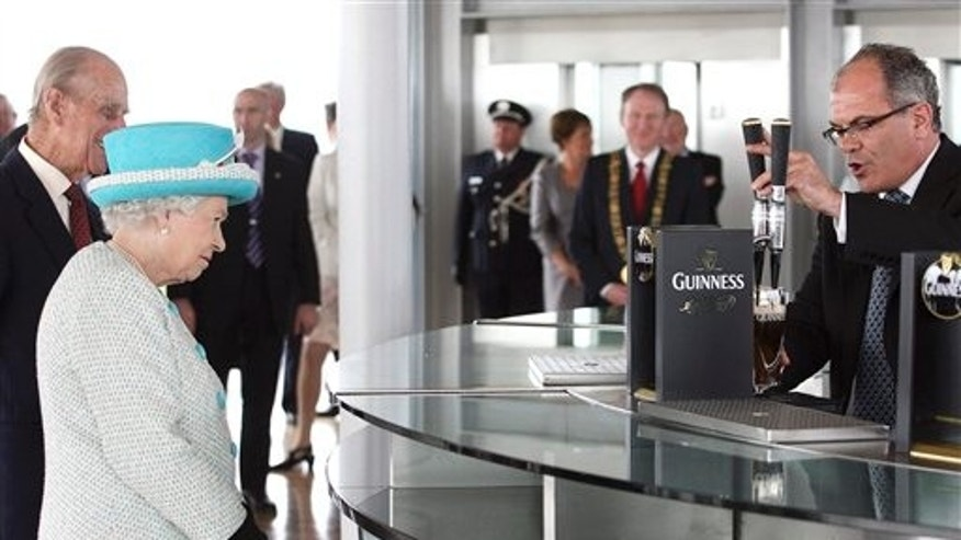 May 18: Britain's Queen Elizabeth II and Prince Philip watch as Fergal Murray pours a pint of Guinness in  the Gravity Bar, during a tour of the Guinness Storehouse, one of Ireland's most popular sites, in Dublin. Both the Queen and Prince Philip, on the second day of the first-ever state visit to Ireland, declined to taste the Irish stout. (AP/Pool)