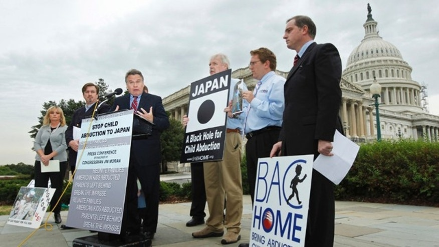 Sept. 29, 2010: In this file photo, Rep. Chris Smith, center, R-N.J. with relatives of American children abducted to Japan, speaks at a news conference on Capitol Hill in Washington, calling for swift passage of a resolution on child abduction to Japan. Japan has taken the first step toward joining an international child custody convention Thursday, May 19, 2011 amid foreign pressure on Tokyo to revise a policy some say allows Japanese mothers to too easily take their children away from foreign fathers.