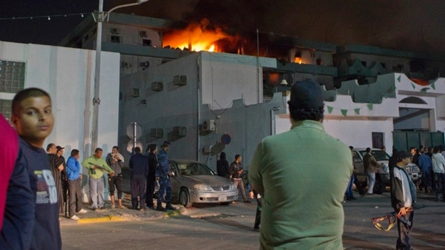 May 17: In this photo taken on a government organized tour, soldiers and civilians gather in front of a burning official building following an airstrike in Tripoli, Libya.