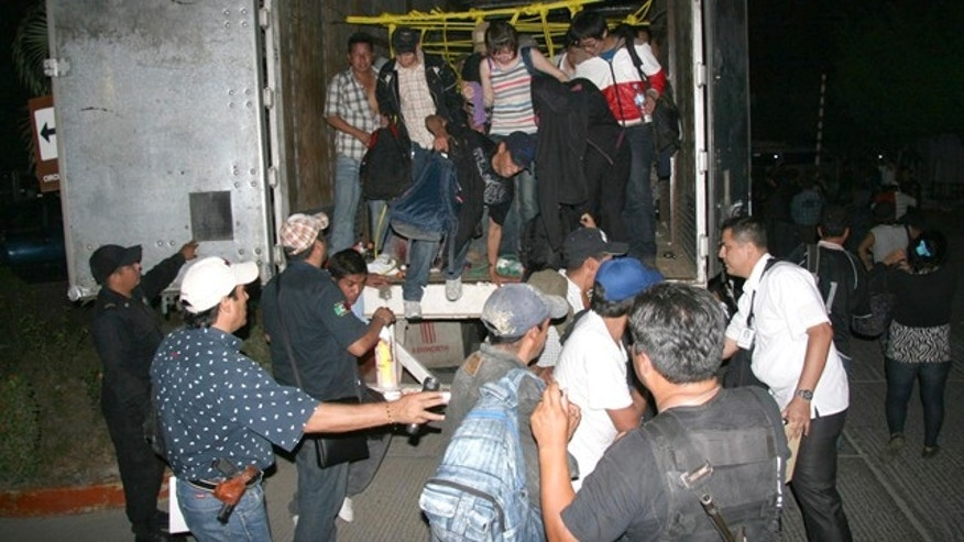 May 17: In this photo released by Chiapas State Attorney General, migrants from Latin America and Asia leave a truck that was heading to the U.S. after being detected by an X-ray equipment at a checkpoint near Tuxtla Gutierrez, in Mexico's southern Chiapas state.