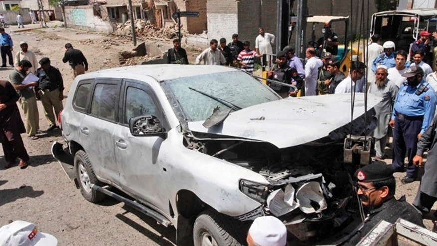 May 20: Pakistani police officers gather around a vehicle damaged in a roadside bomb explosion in Peshawar, Pakistan.
