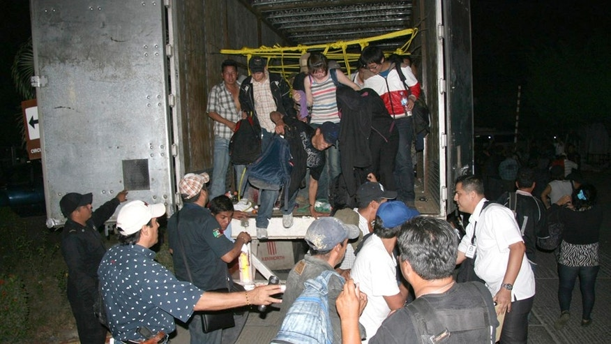 In this photo released by Chiapas State Attorney General, migrants from Latin America and Asia leave a truck that was heading to the US after being detected by an X-ray equipment at a checkpoint near Tuxtla Gutierrez, in Mexico's southern Chiapas state, Tuesday, May 17, 2011. Police in Mexico's southern Chiapas state found over 500 migrants Tuesday inside two trailer trucks. (AP Photo/Chiapas State Attorney General)