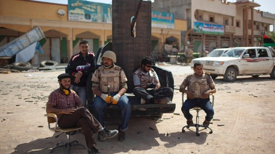 May 23: Rebel fighters rest at the front line between the rebels and Qaddafi forces. For some, a feeling of normalcy is returning to the area.