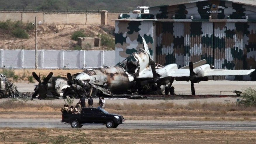 May 23: Pakistani troops gather next to a burnt plane inside the naval aviation base following an attack by militants in Karachi, Pakistan. Pakistani commandos were close to regaining control of a naval base Monday as they hunted for any last holdouts among a team of Taliban militants who attacked and occupied the facility for 15 hours, destroying two U.S.-supplied planes and killing 12 security officers.