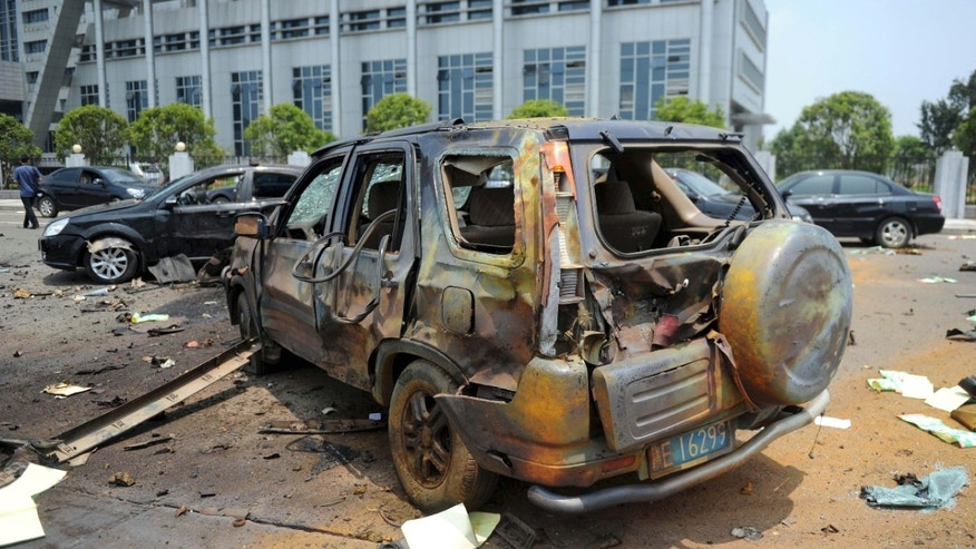 A damaged vehicle sits at the site of an explosion near the Linchuan district government building in Fuzhou city, east China's Jiangxi Province. Hours after homemade bombs blasted government buildings, some Chinese were quick to glorify the disgruntled bomb-setter _ a sign of the bitterness many feel toward the government for chasing growth while neglecting justice.