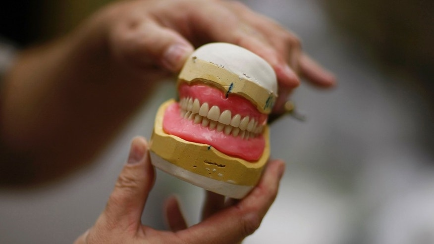 PEMBROKE PINES, FL - JANUARY 12:  David Gikovatyi, the Denture lab manager, works on a new set of dentures at the Affordable Dentures lab on January 12, 2009 in Pembroke Pines, Florida. Statistics show that the number of people loosing all their teeth has declined 60 percent in the United States since 1960. The reduction is attributed to the program of fluoridation begun in the 1940s as well as education on proactive dental hygiene.  (Photo by Joe Raedle/Getty Images) *** Local Caption *** David Gikovatyi