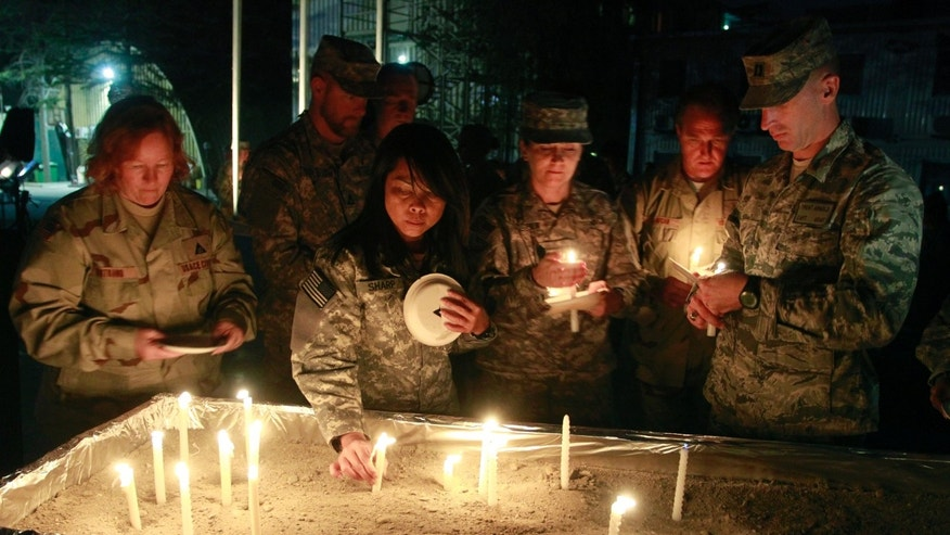 U.S. soldiers place lit candles as they gather to mark Memorial Day at the U.S. Army Corps of Engineers' headquarters in Kabul, Afghanistan on Sunday, May 29, 2011. Some U.S. troops in Afghanistan have held a candlelit remembrance for those lost ahead of Memorial Day.