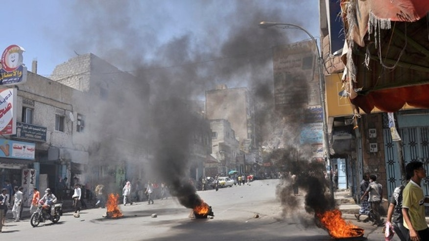 May 31: Burning tyres left by anti-government protestors as they block the road during clashes with Yemeni security forces in Taiz, Yemen.