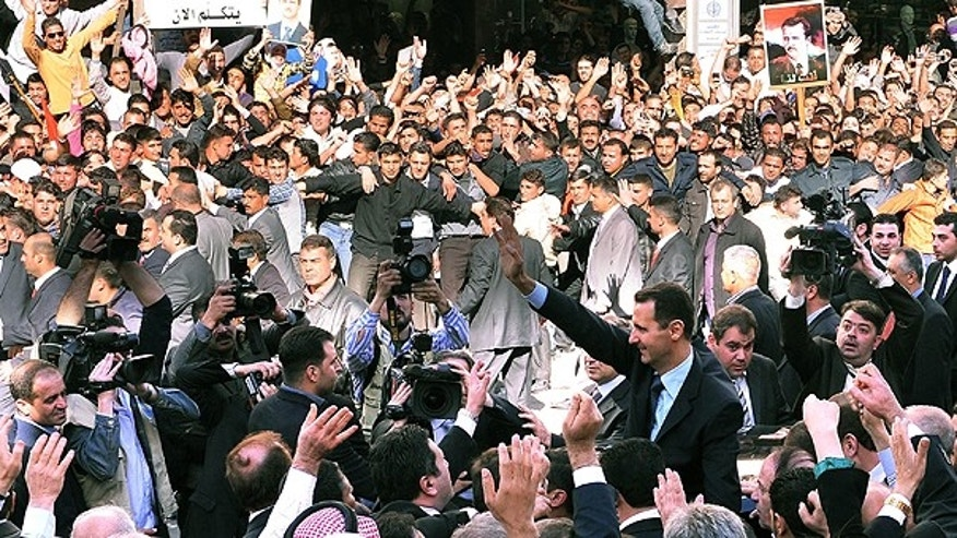 March 30: In this photo released by the Syrian official news agency SANA, Syrian President Bashar Assad, foreground right, waves to his supporters after he made a speech at the Parliament, in Damascus, Syria.