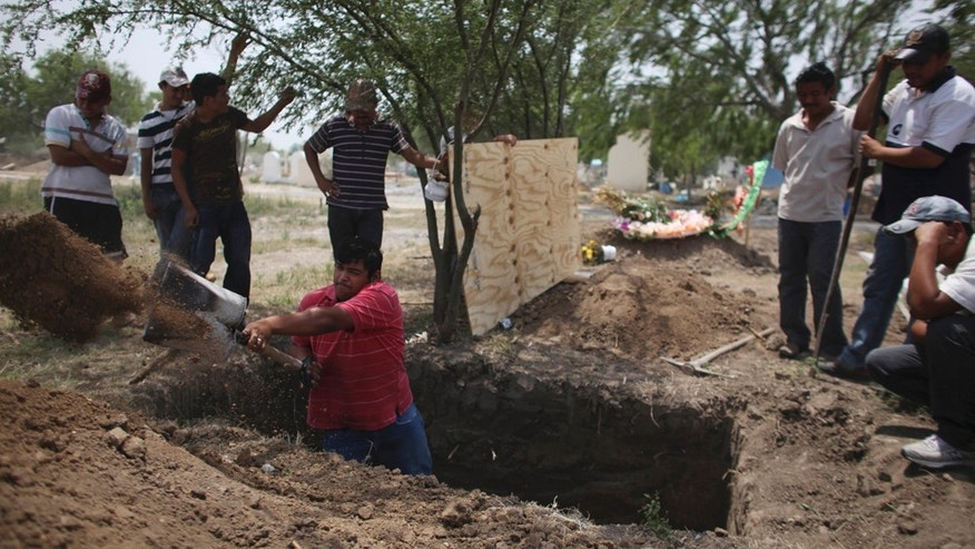 In this photo taken April 27, 2011, family members of Alfredo Espinosa, allegedly killed by unknown assailants, dig a grave at a local cemetery in San Fernando, Mexico. A total of 183 bodies have been found in mass graves near San Fernando, most of them were presumably people kidnapped from buses traveling between Ciudad Victoria and the border town of Matamoros, according to authorities. (AP Photo/Alexandre Meneghini)