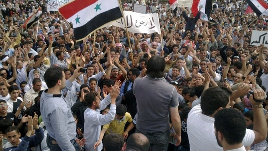 May 29: In this citizen journalism image made on a mobile phone and provided by Shaam News Network, Syrian anti-regime protesters carry national flags and banners during a rally in Talbiseh, in the central province of Homs, Syria.