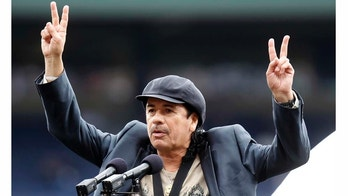 Grammy-winning guitarist Carlos Santana gestures after receiving the Major League Baseball Beacon of Change Award during a pregame ceremony during the annual Civil Rights Games before the Atlanta Braves game against the Philadelphia Phillies, Sunday, May 15, 2011, in Atlanta. (AP Photo/John Bazemore)