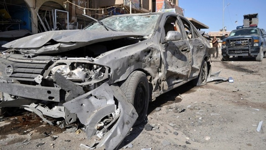 June 3: The remains of a vehicle damaged in an explosion are seen the morning after four blasts killed several people in Ramadi, 70 miles west of Baghdad, Iraq.