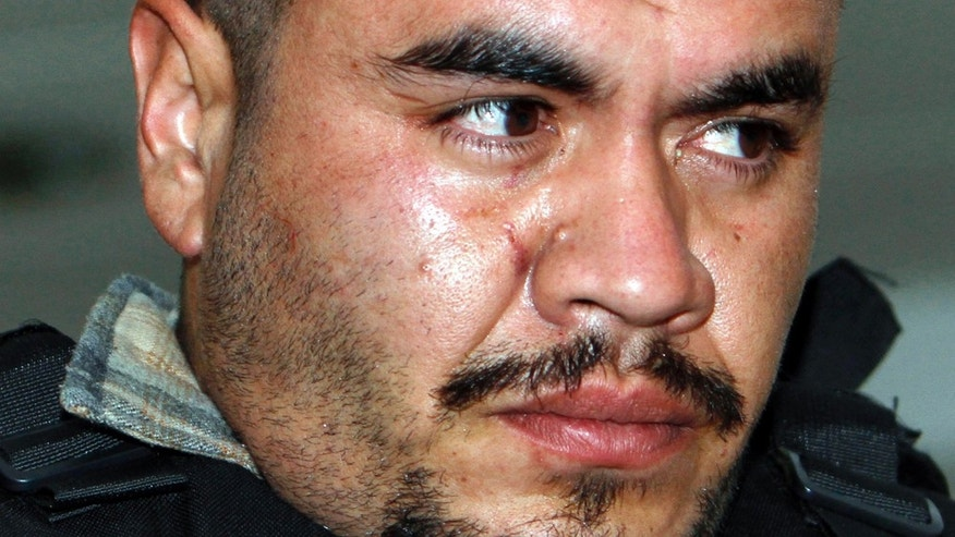"FILE - In this April 17, 2011 file photo, Martin Estrada Luna, known as ""El Kilo,"" is prestented to the press in Mexico City. When he was deported from the U.S. to Mexico for the third time, Luna was a high school dropout with a rap sheet of petty crimes like burglary. Less than two years later, Mexican authorities say, he has transformed himself into a drug baron known as El Kilo, the leader of a ruthless cell of the Zetas gang who masterminded the mass killings of more than 250 people. He is now under arrest in Mexico City. (AP Photo/Marco Ugarte, File)"