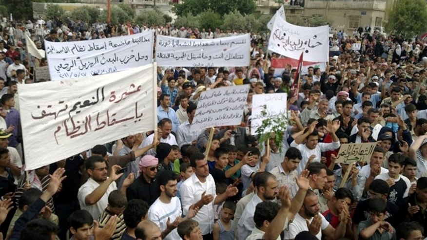 May 29: In this citizen journalism image made on a mobile phone and provided by Shaam News Network, Syrian anti-regime protesters carry banners during a rally in Talbiseh, in the central province of Homs, Syria.