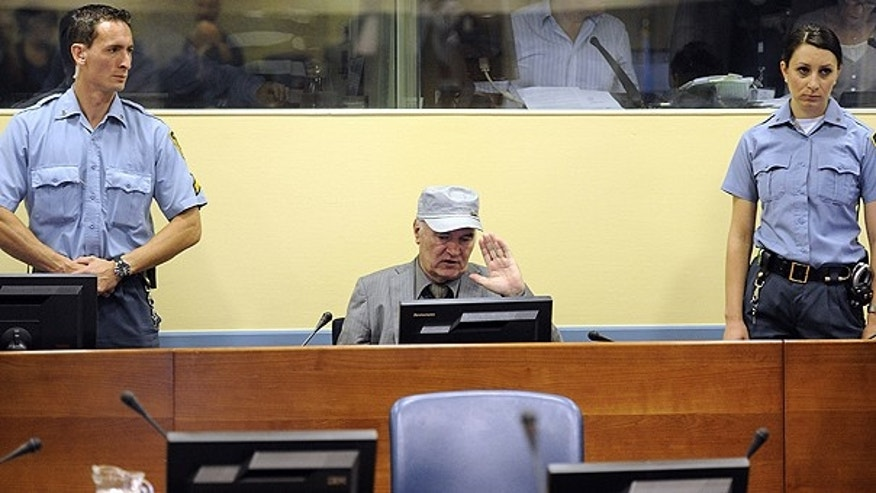 June 3: Former Bosnian Serb Gen. Ratko Mladic, center, salutes between officers standing guard in the court room during his initial appearance at the U.N.'s Yugoslav war crimes tribunal in The Hague, Netherlands.