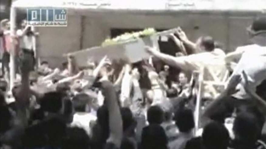 People shout slogans as a coffin is lifted onto a vehicle during a funeral for what was believed to be a person killed in the latest crackdown on protests in the city of Homs. This still image was taken from video uploaded on a social media website May 21, 2011.