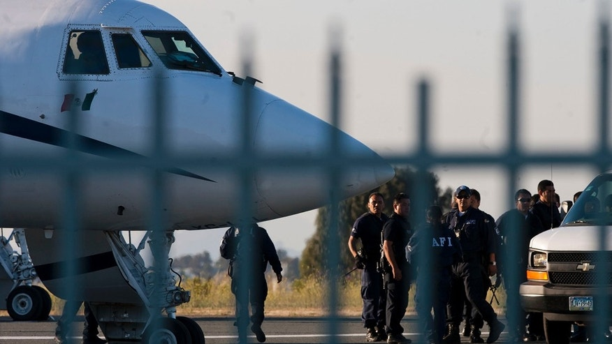 Federal police officers stand next to an airplane after the early morning arrest of former Tijuana Mayor Jorge Hank Rohn in the city of Tijuana, Mexico, Saturday June 4, 2011. Hank Rhon, one of Mexico's most flamboyant businessmen and politicians, has been detained on suspicion of illegal weapons possession, the federal Attorney General's Office has announced. (AP Photo/Francisco Vega)