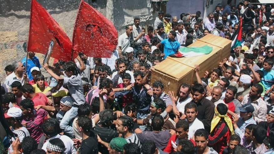 June 6: Palestinian mourners carry the coffin of a Palestinian protester who was killed when Israeli soldiers opened fire on Sunday at protesters who tried to burst across Syria's frontier with the Israeli-controlled Golan Heights, during a funeral procession at Khan al-Shih Palestinian refugee camp, some 25 kilometers far from Damascus, Syria.