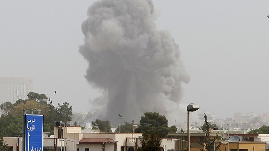 June 7: A smoke and dust cloud from an explosion rises into the sky after a NATO airstrike in Tripoli, Libya.