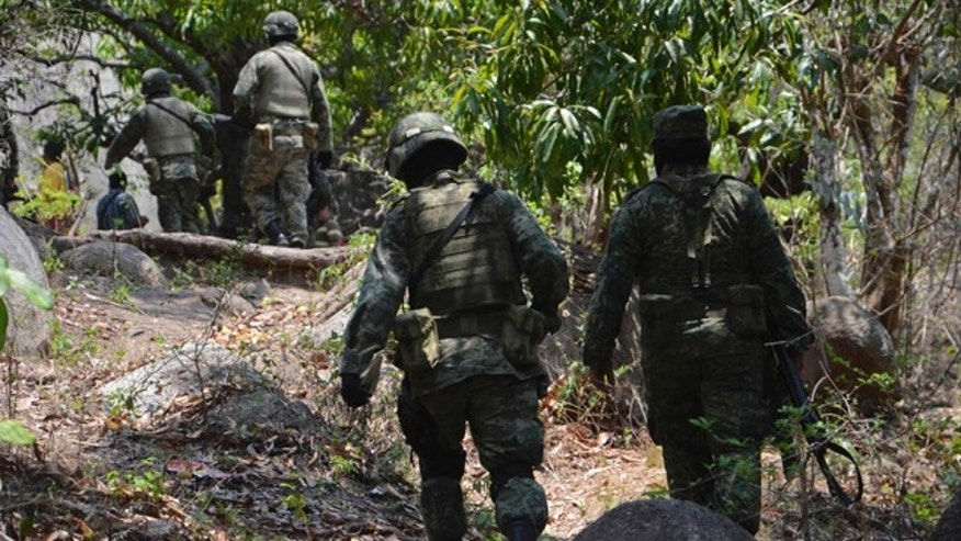 June 8: Army soldiers walk toward a site in response to a report of mass graves in the Pacific resort city of Acapulco, Mexico.