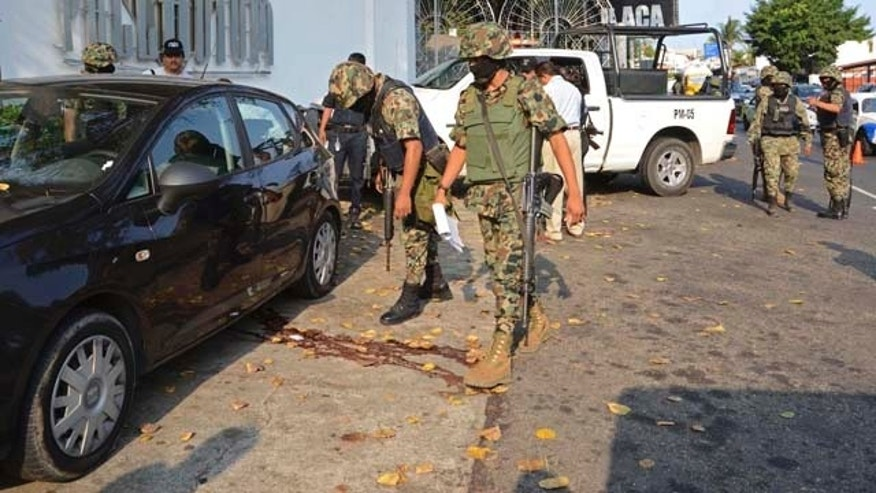 Mexican navy sailors inspects the car where three bodies were found outside of a discotheque in the Pacific resort city of Acapulco, Mexico, Thursday May 26, 2011. Two women and a man were found dead of gunshot wounds inside the car. The vehicle had been previously reported as stolen. (AP Photo/Bernandino Hernandez)