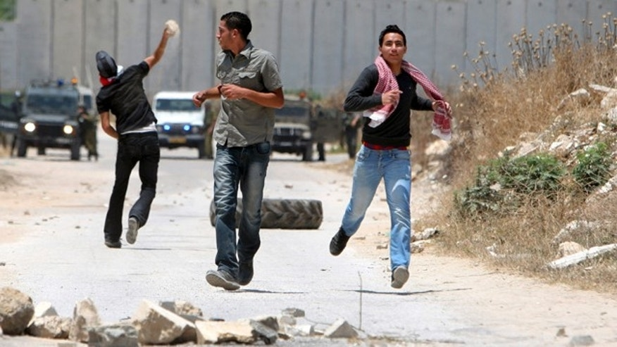 June 7: Palestinian demonstrators run after hurling stones at Israeli troops, during clashes in the northern West Bank village of Nazlet Issa.