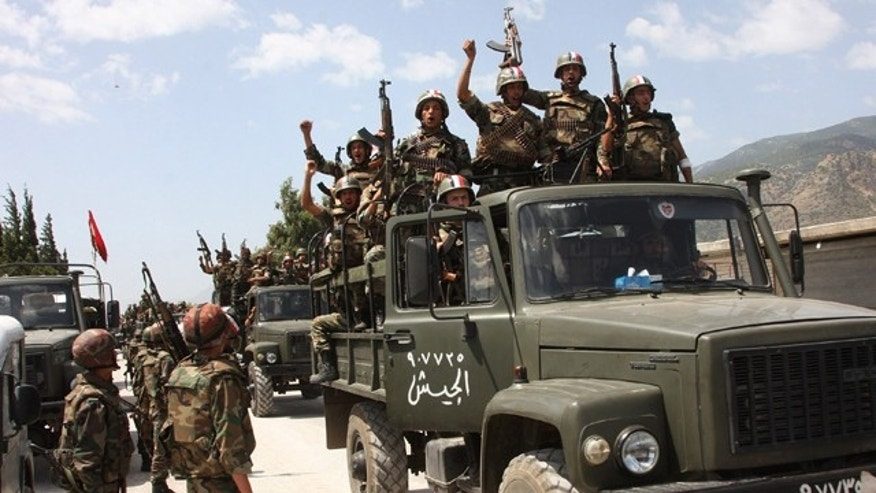 June 10: In this photo taken during a government-organized visit for media, Syrian army soldiers standing on their military trucks shout slogans in support of Syrian President Bashar Assad, as they enter a village near the town of Jisr al-Shughour, north of Damascus, Syria.