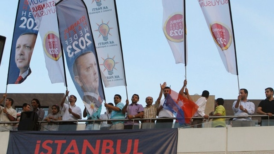 "June 12: Supporters of Turkish Prime Minister Recep Tayyip Erdogan react outside the AK party offices in Istanbul. Turkey's ruling party sought a third term in elections Sunday, aiming to build on economic and diplomatic advances in recent years as well as introduce a new constitution it says will make the country more democratic. The banner reads ""Istanbul is ready for 2023 target."""