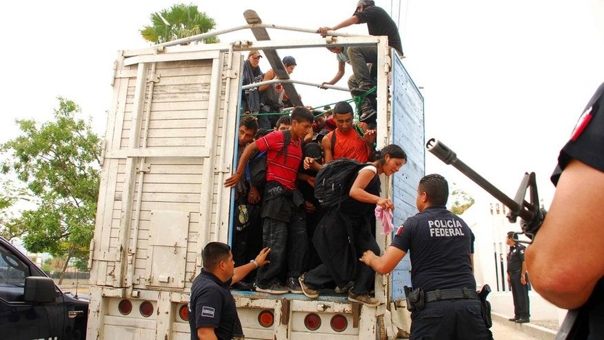 June 12: Migrants jump out of a tractor trailer as Mexican federal police watch at police headquarters in Tuxtla Gutierrez, Mexico. (AP Photo/Alejandro Estrada)