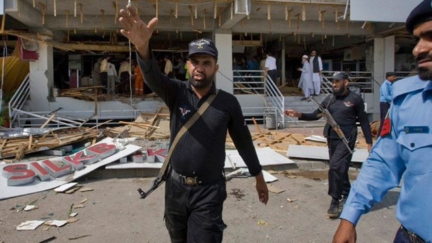 June 13: A Pakistan police officer gestures towards the media from the site of suicide bombing in Islamabad, Pakistan.