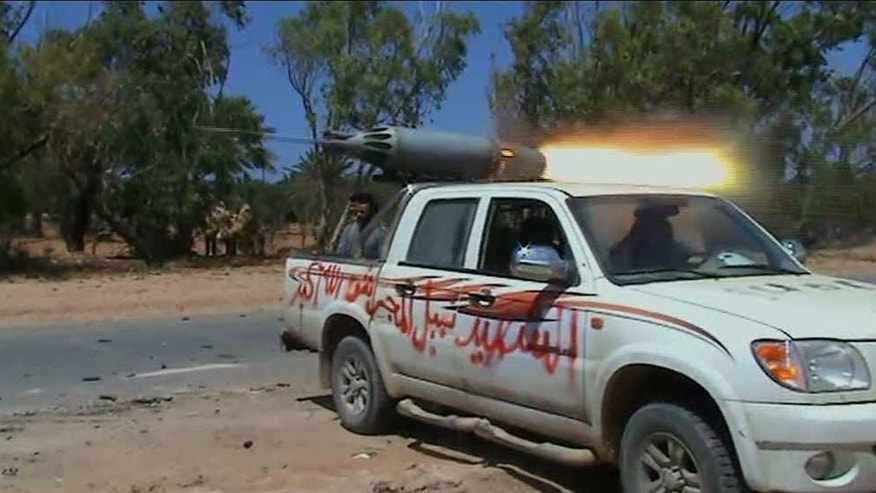 June 12: In this image taken from TV, showing rebel forces on the front line as they repel government troops, in Dafniya, Libya, as fighting continued on Sunday near Libya's main port of Misrata, a western redoubt of the rebels.  Video of the battle shows rebels advancing down a road, firing automatic weapons, guns mounted on pick up trucks, rockets and heavy artillery. (AP/APTN)