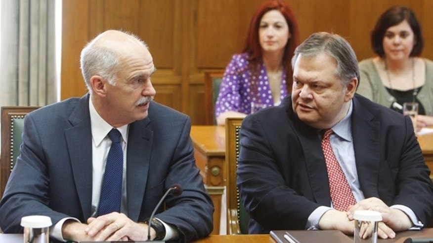 June 17: Greek Prime Minister George Papandreou, left, talks with his newly-appointed finance minister Evangelos Venizelos, right, during the first cabinet meeting of the newly-appointed Greek government, at the parliament in central Athens.