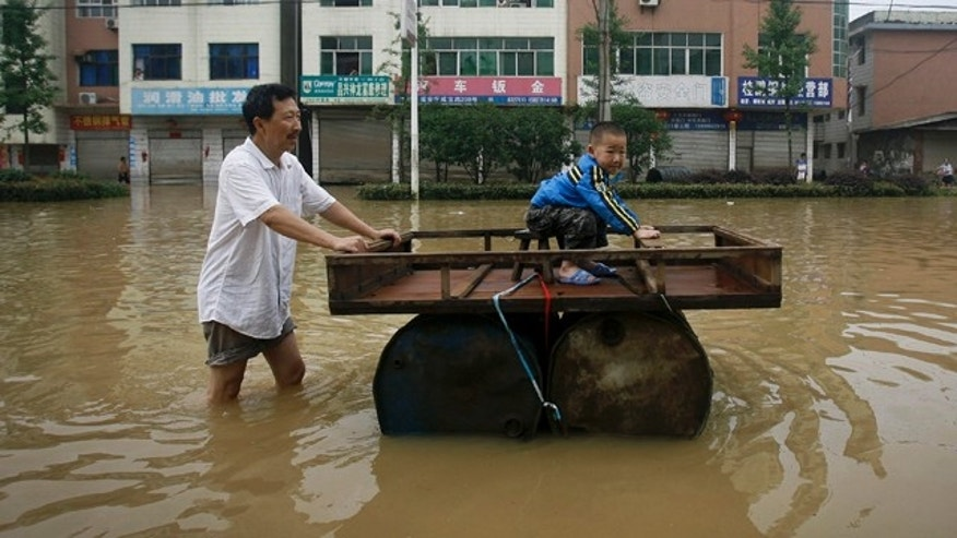 June 15: A Chinese man pushes a makeshift drum raft while a child sits on it in a flooded street in Xianing city in central China's Hubei province.