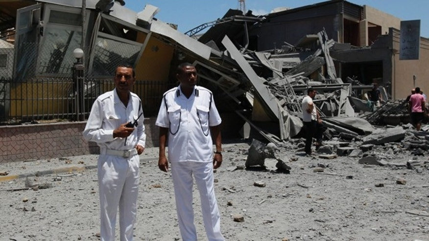 June 16: Libyan police officers stand next to a destroyed building in what officials said was a NATO airstrike at a hotel, in Tripoli, Libya.