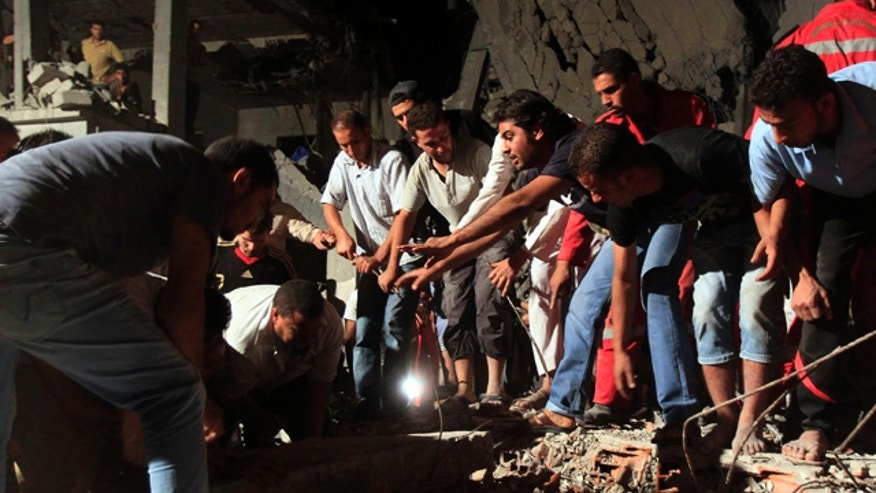 June 19: In this photo taken on a government-organized tour, Libyan firefighters and local residents remove debris from a damaged residential building.