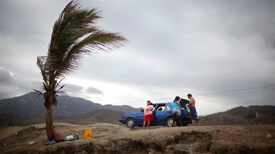 June 20: A family prepares to leave Miramar beach after having a picnic before the arrival of Tropical Storm Beatriz in the Pacific resort city of Manzanillo, Mexico. (AP Photo/Alexandre Meneghini)