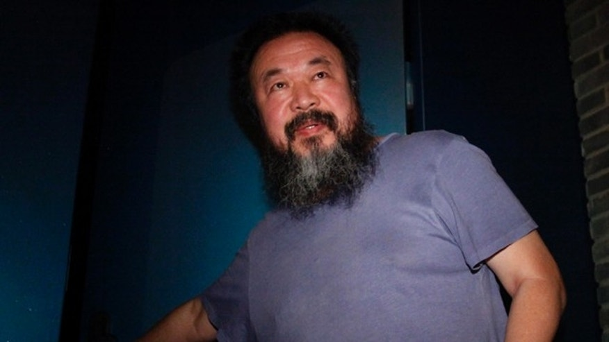 June 22: Activist artist Ai Weiwei opens the gate to his home after returning from detention in Beijing, China.