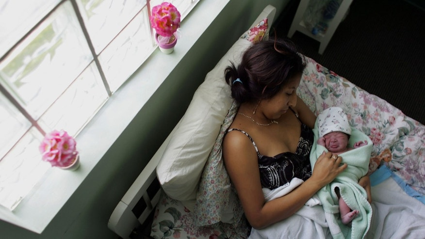 FLORIDA CITY, FL- OCTOBER 16:  Yailin Melissa Turcios, who was about 20 minutes prior, lies in the arms of her mother, Rosa Turcios, on a bed at the Birthing Center of South Florida October 16, 2006 in Florida City, Florida. (Photo by Joe Raedle/Getty Images)