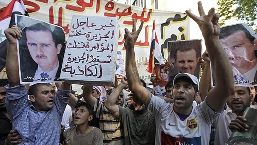 June 24: Lebanese and Syrian protesters shout slogans as they carry pictures of Syrian President Bashar Assad and Syrian flags, during a demonstration to show their support for the Syrian President in front of the Syrian embassy in Beirut, Lebanon.