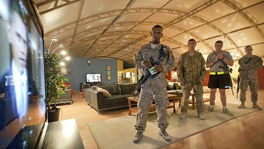 June 23: Spc. Gavin Fruge, 22, of Crowley, La., left, watches a rebroadcast of President Obama's speech on proposed troop withdrawal with fellow soldiers at Kandahar Airfield in Kandahar, Afghanistan.